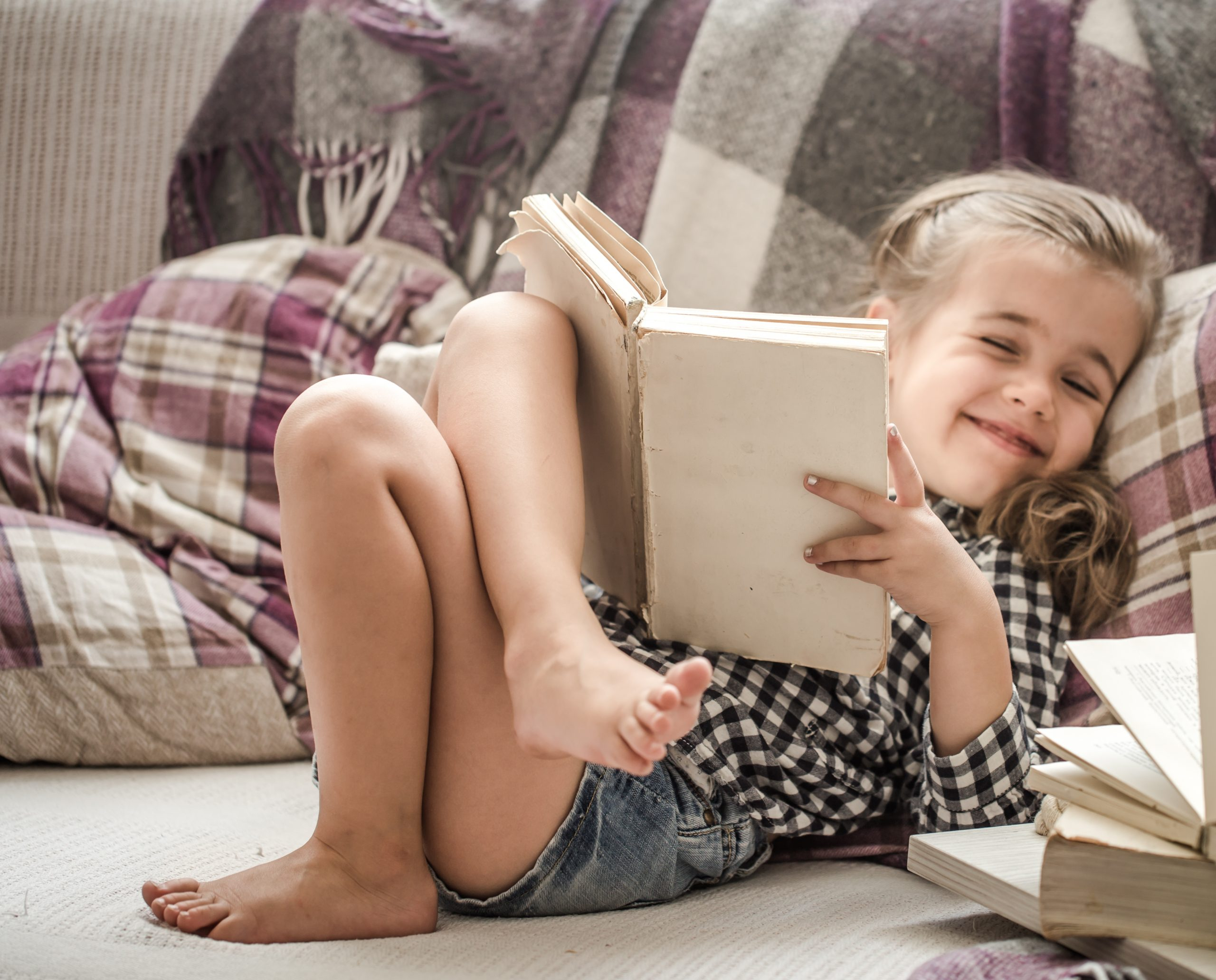 little cute girl reading a book on the couch , the concept of education and recreation